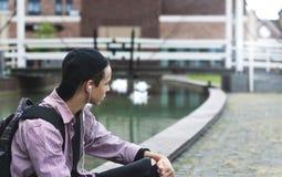 Hombre joven que escucha la música que se sienta en la acera Imágenes de archivo libres de regalías
