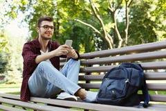 Hombre joven que escucha la música que se sienta en parque fotos de archivo libres de regalías