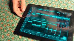 Hombre joven que escucha su música preferida en la tableta almacen de video