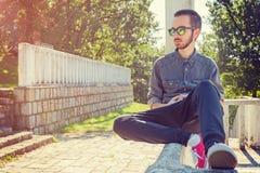 Hombre joven que espera alguien en el parque Foto de archivo libre de regalías