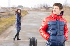 Hombre joven que espera en el camino con una maleta Fotografía de archivo