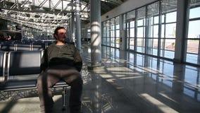 hombre joven que espera su vuelo en salón del aeropuerto metrajes
