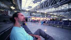 hombre joven que espera su vuelo en salón del aeropuerto almacen de metraje de vídeo