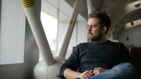 hombre joven que espera su vuelo en salón del aeropuerto almacen de video