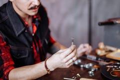 Hombre joven que estima la calidad del diamante imagen de archivo libre de regalías