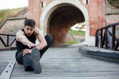 Hombre joven que estira y que se relaja después del entrenamiento imagen de archivo libre de regalías
