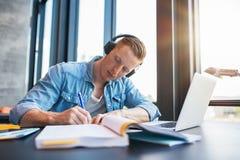 Hombre joven que estudia en biblioteca de universidad Foto de archivo