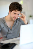 Hombre joven que estudia en casa Imagen de archivo