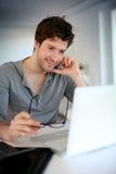 Hombre joven que estudia en casa en el ordenador portátil Foto de archivo