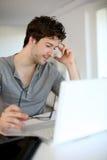 Hombre joven que estudia en casa en el ordenador portátil Foto de archivo libre de regalías