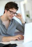 Hombre joven que estudia en el ordenador portátil Imagen de archivo