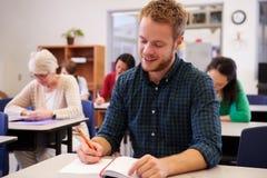 Hombre joven que estudia en una clase de la enseñanza para adultos Fotografía de archivo