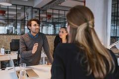 Hombre joven que explica el nuevo plan empresarial a los compañeros de trabajo Imagen de archivo libre de regalías