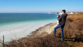 Hombre joven que filma un seaview hermoso y una costa costa cliffed en la cámara de la acción almacen de metraje de vídeo