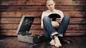 Hombre joven que finge escuchar un gramófono viejo en casa almacen de metraje de vídeo