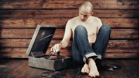 Hombre joven que finge escuchar un gramófono viejo en casa almacen de video