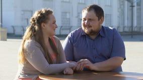Hombre joven que frota ligeramente la mano de la novia, fecha romántica en café al aire libre, proximidad almacen de metraje de vídeo