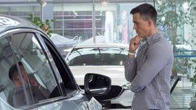 Hombre joven que frota su barbilla cuidadosamente, eligiendo el nuevo coche para comprar en la representación metrajes