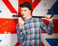 Hombre joven que fuma con el bastón en su hombro Foto de archivo
