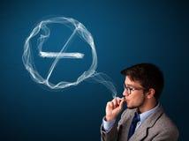 Hombre joven que fuma el cigarrillo malsano con la muestra de no fumadores Fotos de archivo libres de regalías