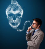Hombre joven que fuma el cigarrillo peligroso con humo tóxico del cráneo foto de archivo