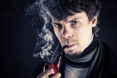 Hombre joven que fuma un tubo Fotos de archivo