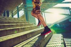 Hombre joven que funciona con para arriba las escaleras al aire libre en la ciudad Fotografía de archivo libre de regalías