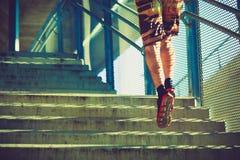 Hombre joven que funciona con para arriba las escaleras al aire libre en la ciudad Foto de archivo