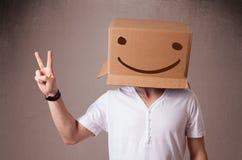 Hombre joven que gesticula con una caja de cartón en su cabeza con smiley Imágenes de archivo libres de regalías