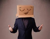 Hombre joven que gesticula con una caja de cartón en su cabeza con smiley Fotos de archivo