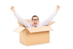 Hombre joven que gesticula felicidad profundamente dentro de una caja Foto de archivo libre de regalías