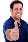 Hombre joven que gesticula los pulgares para arriba Fotografía de archivo