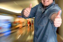 Hombre joven que gesticula los pulgares para arriba en la alameda de compras Foto de archivo