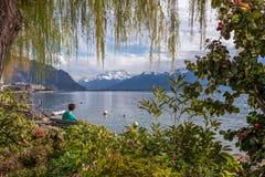 Hombre joven que goza con la opinión espectacular sobre las montañas de las montañas y el lago geneva Imagen de archivo