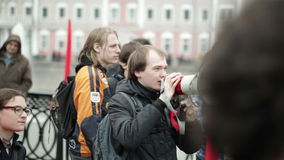 Hombre joven que grita con un megáfono en la manifestación de la protesta almacen de video