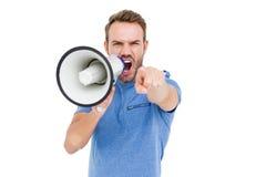 Hombre joven que grita en el altavoz de cuerno Foto de archivo libre de regalías
