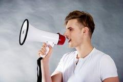 Hombre joven que grita en megáfono Imágenes de archivo libres de regalías