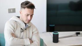 Hombre joven que habla al ayudante electrónico elegante del hogar del altavoz