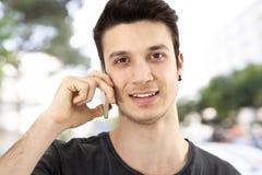 Hombre joven que habla el teléfono móvil en la calle Imágenes de archivo libres de regalías