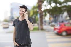 Hombre joven que habla el teléfono móvil en la calle Foto de archivo