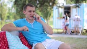 Hombre joven que habla en el teléfono al aire libre almacen de video