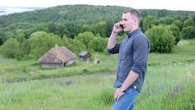 Hombre joven que habla en el teléfono al aire libre almacen de metraje de vídeo