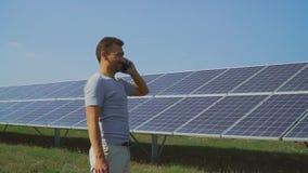 Hombre joven que habla en el teléfono en el campo con los paneles solares metrajes