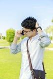 Hombre joven que habla en el teléfono con el pequeño bolso Fotos de archivo