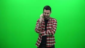 Hombre joven que habla en el teléfono contra una pantalla verde almacen de video