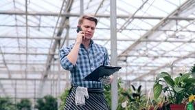 Hombre joven que habla en el teléfono en invernadero metrajes