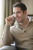 Hombre joven que habla en el teléfono inalámbrico en casa Fotos de archivo