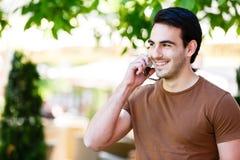 Hombre joven que habla en el teléfono mientras que coloca el jardín cercano del ` s del café Foto de archivo