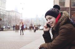 Hombre joven que habla en el teléfono que se sienta en la acera Imagen de archivo