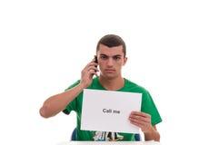 Hombre joven que habla en móvil y que sostiene en su mano un papel con Imágenes de archivo libres de regalías
